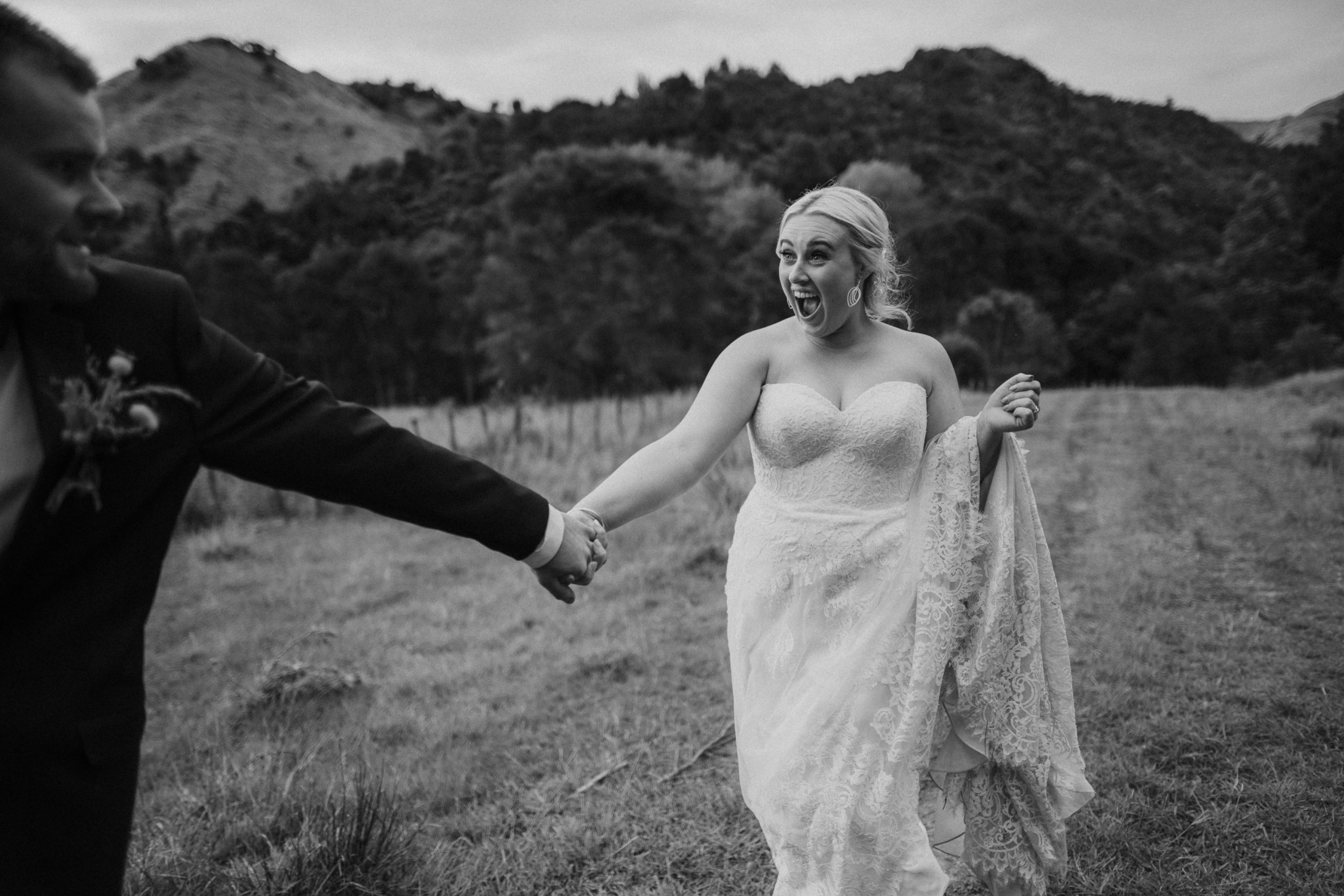 Bride and Groom walking on a farm by New Zealand wedding photographer Binh Trinh with Monique