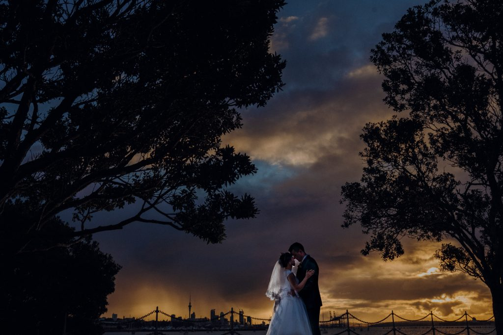Auckland sunset wedding photo with Auckland Sky Tower in the background