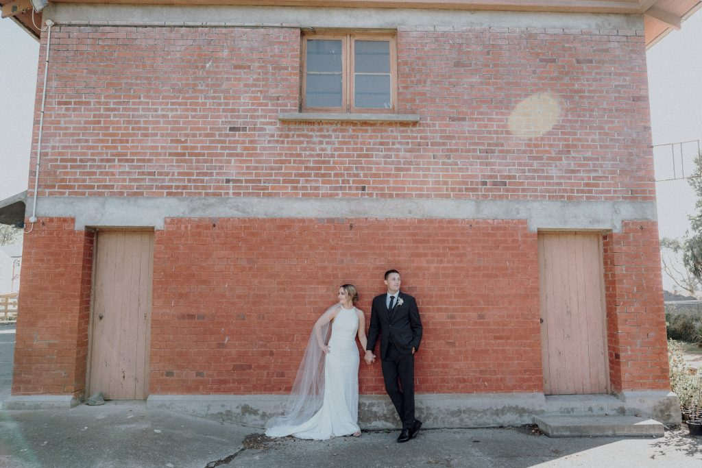 bride and groom infront of brick wall by Manawatu wedding photographer Binh Trinh