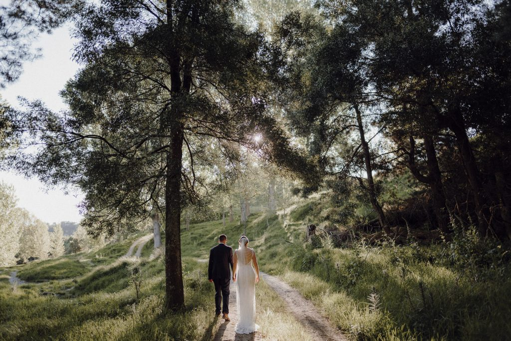 A timeless wedding bridal portrait of couple walking in the forest at Makoura Lodge wedding venue