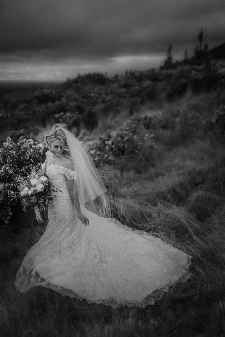 A stunning black and white New Zealand wedding photograph of a bride on a hill top