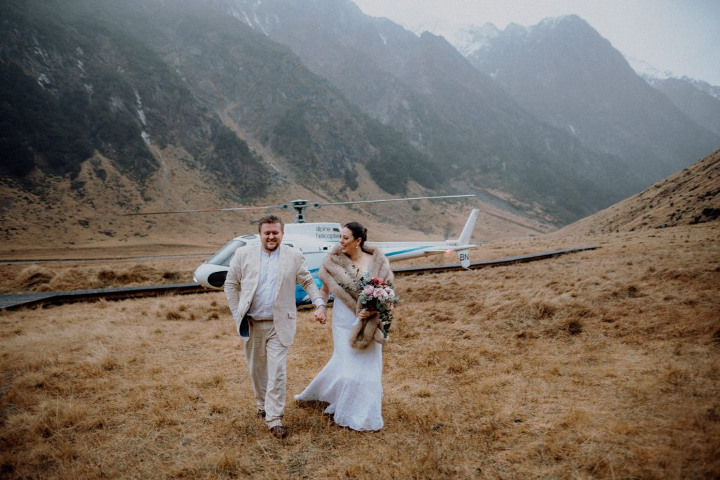 A couple stepping of a helicopter at Minaret Station for their Queenstown Elopement Photography by Binh Trinh