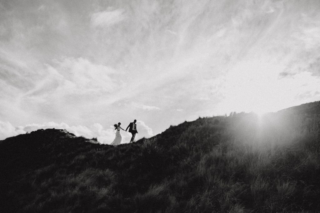 Wedding photography of Bride and Groom walking along the hill top at Roy's Peak in Lake Wanaka, Queenstown